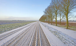 Snowy road through the countryside Stock Images