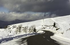 A snowy road curve in the mountains with a cloudy sky - horizont Stock Photos