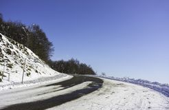 A snowy road curve in the mountains with a large graduated blue Royalty Free Stock Photos