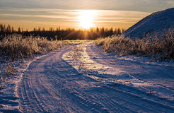 Snowy road disappearing into the sunset. Royalty Free Stock Photos