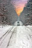 Snowy road through the forest in the countryside from Netherlands. Snowy road through the forest in the countryside from the Netherlands at sunset Royalty Free Stock Photo