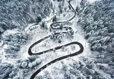 Snowy road in the forest. Extreme winding road high up in the mo stock photography