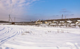 Snowy road and houses on the edge of the village. Royalty Free Stock Images