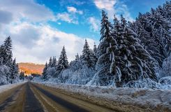Snowy road through mountains in evening. Wonderful nature scenery in winter Royalty Free Stock Photo