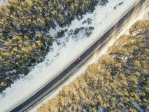 Snowy road with a moving car in winter stock photo