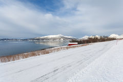 Snowy road next to a Norwegian fjord Royalty Free Stock Image