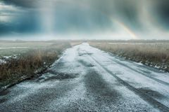 Snowy road with a rainbow Royalty Free Stock Photography
