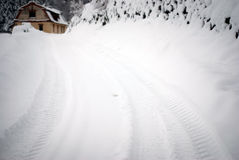 Snowy road. A snow bound road that leads to a cottage Royalty Free Stock Photo
