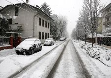 Snowy road during a snowfall in the city with some cars royalty free stock photos