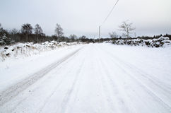 Snowy road surrounded of stone walls Stock Photo