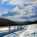 Snowy road to coniferous forest in mountains. Winter mountain landscape. winding road that leads into the pine forest covered with snow. wooden fence stands near stock photos