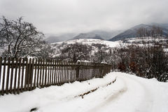 Snowy road to village in mountains Royalty Free Stock Photos
