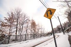 Snowy Road U Turn. U-turn sign on snowy road in urban area during winter stock image