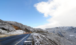 Snowy road under freezing blue sky. With snow mountain in Sichuan, China Royalty Free Stock Photos