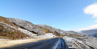 Snowy road under freezing blue sky. With snow mountain in Sichuan, China Stock Photo
