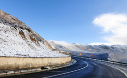 Snowy road under freezing blue sky Stock Images