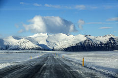 Snowy road with volcanic mountains in wintertime Stock Image