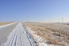 Snowy road with wind turbines and Street lamps Royalty Free Stock Photo