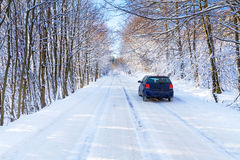 Snowy road in winter forest with single car. Of Poland Stock Photos