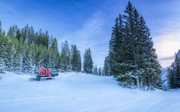 Snowy roads through alpine forest, in Austria. Winter scenery with lots of snow over the forestry roads in the Austrian Alps mountains and two snow groomer Stock Photo
