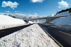 Snowy roads and bridge. Winter season, snowplows and long asvalt road royalty free stock images