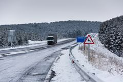 Snowy roads and truck. Winter season, snowplows and long asvalt road royalty free stock photos