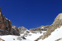 Snowy rocks and cloudless blue sky with moon Royalty Free Stock Photo