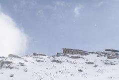 Snowy rocks on mountains Stock Photos