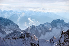 Snowy rocky mountain range. Aerial panorama of a rocky snow-covered mountain range with mountain peaks in a background Royalty Free Stock Photography