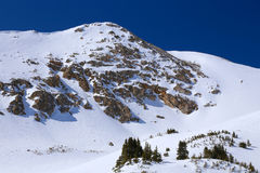Snowy rocky mountain in winter with blue sky and rock stock photography