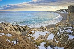 Snowy and rocky overlook of the ocean and beach during winter stock images