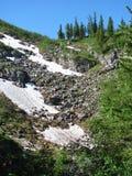 Snowy rocky slope against the blue sky stock photos