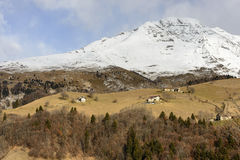 Snowy rocky slopes of Arera peak border green glades with lodges Royalty Free Stock Photo