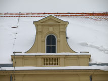 Snowy roof of the church. Roof covered with snow and the window Royalty Free Stock Photo
