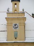 Snowy roof of the church. Church tower with a clock and a window on a snowy day Stock Photo