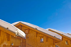 Snowy roofs of mountain wooden cabins Stock Image