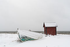 Snowy rowing boat and a boathouse Stock Photography