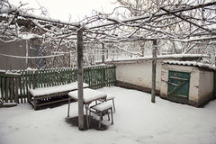 Snowy rural courtyard with homemade table, chairs and bench Stock Photo