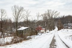 Snowy rural landscape in Appalachia. Harrisville, Ohio/USA-January 9, 2019: A snowy winter countryside landscape including an old barn, a red farmhouse and a stock photography