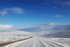 Snowy Rural Road. Landscape of a snowy icelandic road in the middle of the winter wilderness. Features mountains and clear bright blue sky stock photography