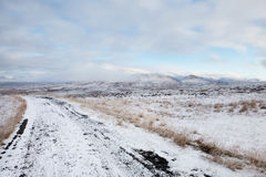 Snowy Rural Road. Landscape of a snowy icelandic road in the middle of the winter wilderness. Features mountains and cloudy sky royalty free stock photos