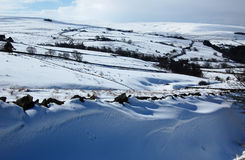 Snowy scene near Allendale, Northumberland, England. Beautiful snow scene and rolling hills near Allendale. Northumberland. The top of a stone wall is only just Stock Images