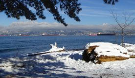Snowy scene of Spanish Banks in Vancouver with the north shore mountains in distance. A sunny and wintry day on the snowy beach of Spanish Banks in the Vancouver royalty free stock photography