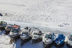 Snowy sea shore, the frozen sea. Boats in the snowy harbor. Around the frozen sea, white ice. Marina, parking for yachts, boat station. Spring is coming. Bright stock photos