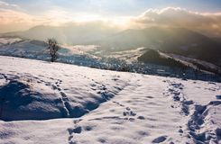 Snowy slope in mountainous countryside. Gorgeous weather with clouds over the mountain ridge Stock Photo