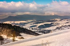 Snowy slope in mountainous countryside. Gorgeous weather with clouds over the mountain ridge Royalty Free Stock Images
