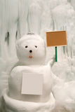Snowy snowman with blank sign Royalty Free Stock Photography