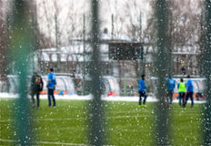 Snowy soccer field in December, frost and cold weather. Young people play football. Selective focus Royalty Free Stock Photo