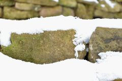 Snowy stone wall. Stones covered with snow. Stock Image