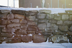 Snowy stone wall in the sun Stock Photos